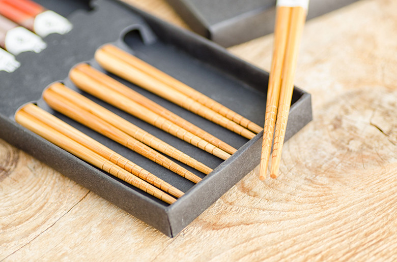 Chinese bamboo chopsticks in black box on wooden background.