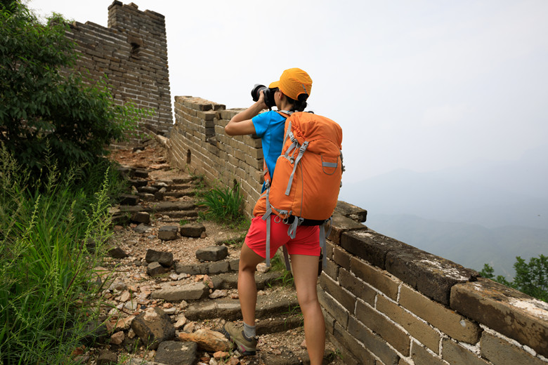 young woman photographer taking photo on great wall