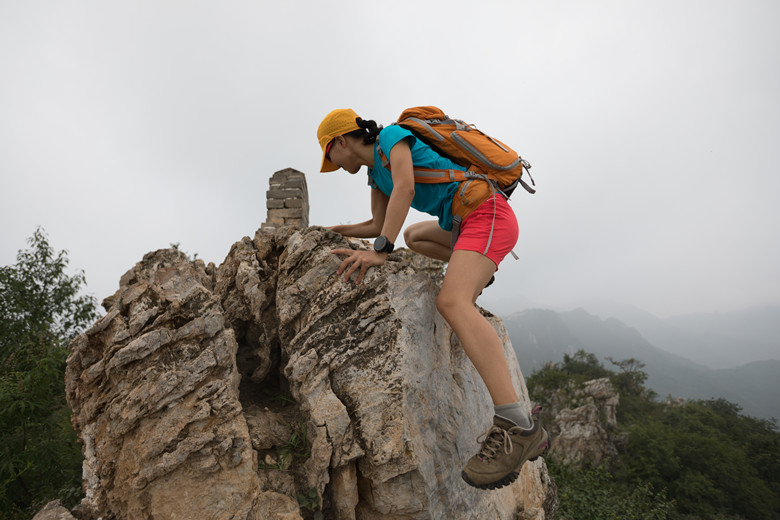 successful woman climber climbing rock on the top of mountain