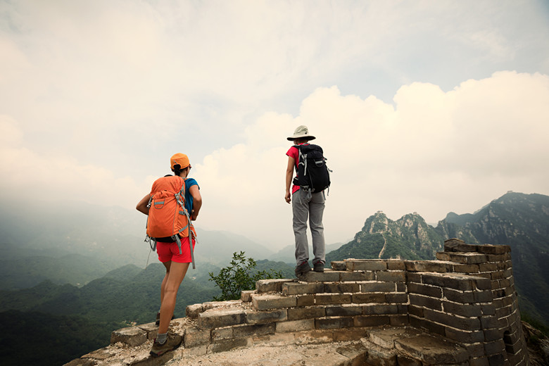 two successful women hikers enjoy the view on the top of great wall