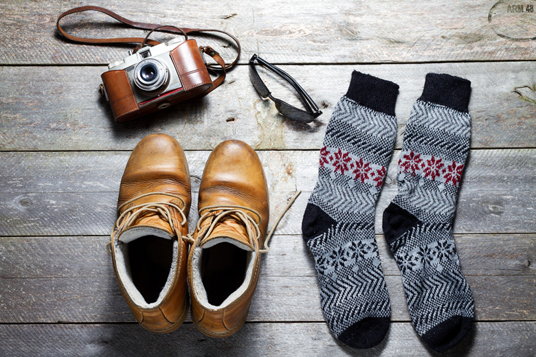 Old boots,socks, photo camera and sunglasses on rustic table