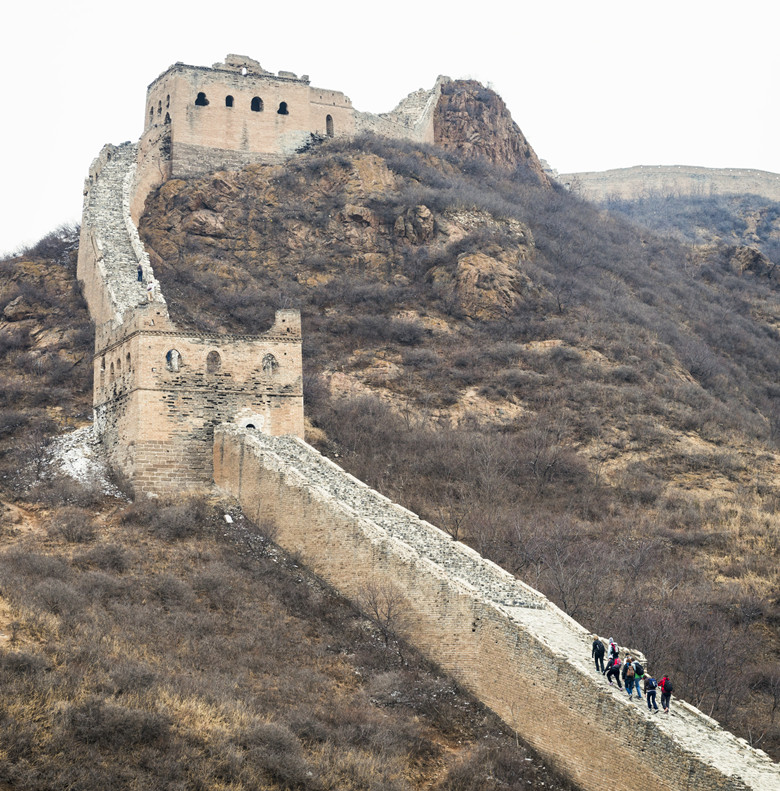 Jinshangling, China - March 19, 2013: A group of tourists ascending a steep section of the Great Wall Of China between Jinshangling and Simatai. A group hiking up a challenging section of the Great Wall of China.