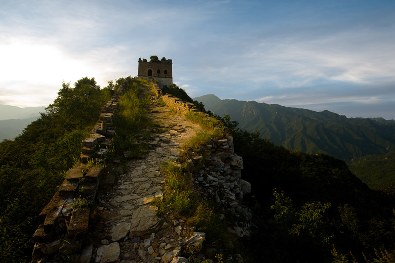 The sun sets fiery red behind a watchtower at the Jiankou section of the Great Wall of China.