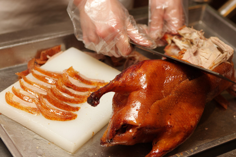Chinese cook prepares Peking Roast Duck. Peking Duck is a famous duck dish from Beijing that has been prepared since the imperial era, and is now considered one of China's national foods.