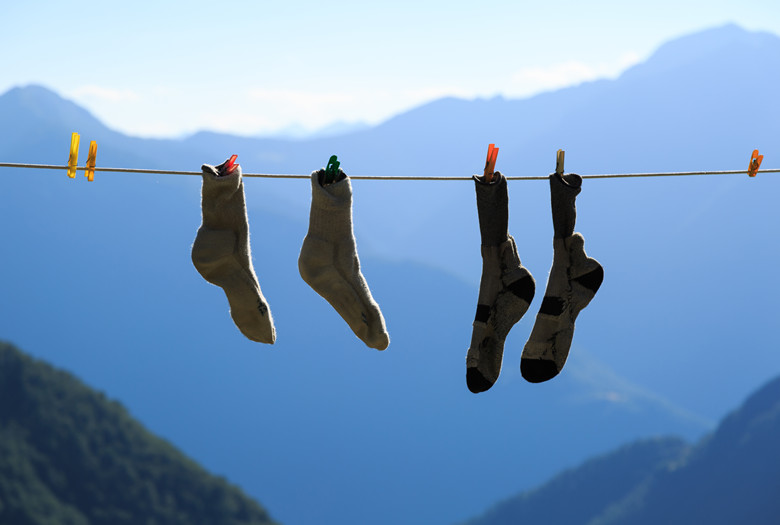 Two pair of socks drying on a clothes line during an adventurous hike in the mountains.