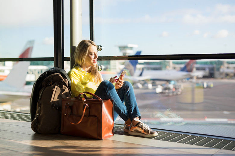 Woman sitting in airport and waiting for her flight, woman using phone in airport departure area
