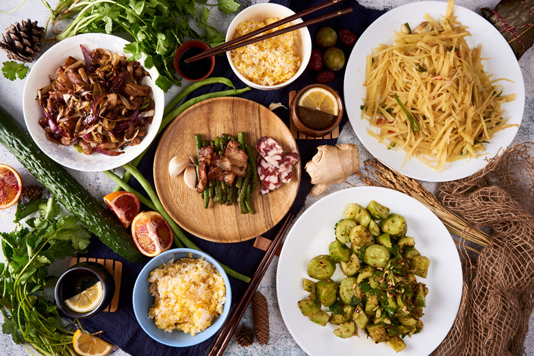 Chinese home made meal: Overhead flat lay. Four dishes, rice and decoration. Striped potatoes, Cucumber with garlic, fried green beans, fried pork with red onions