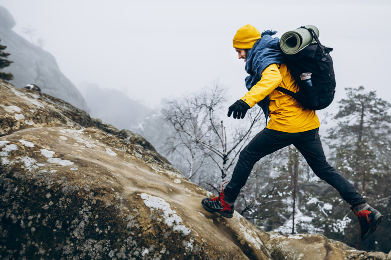 Man in yellow jacket climbs the rocks in the winter mountains