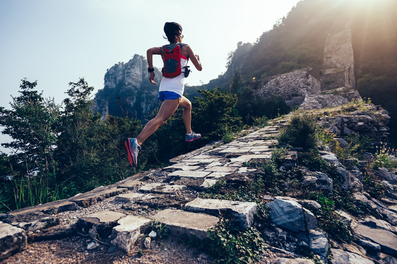 Sporty fitness woman runner running on mountain top