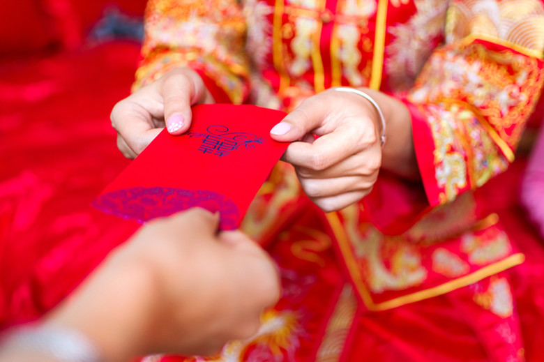 Chinese bride giving red pocket lucky money in the wedding