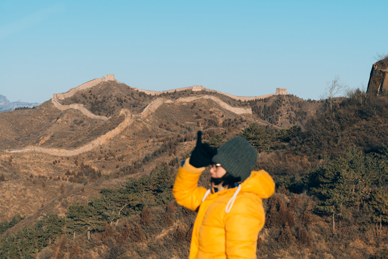 Asian woman hiking on mountain path into the Great Wall Of China at Simatai Great Wall looking forward with hand on forehead- World heritage site-Beijing- China- Traveling adventure- outdoor activity