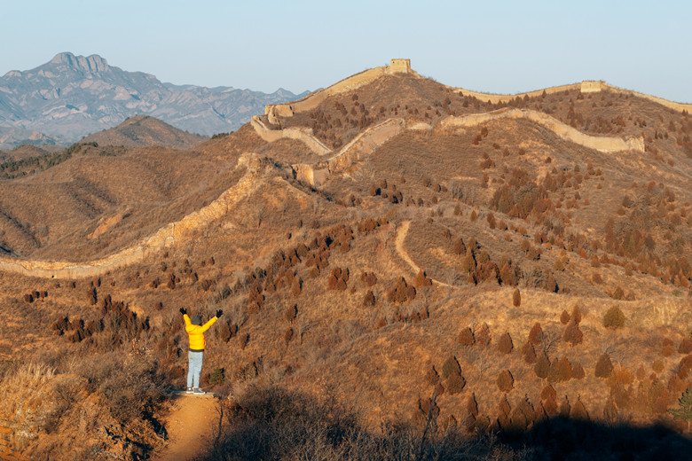 Woman hiking from rear view raises arms to celebrate with feeling good-relax- freedom in Great Wall Of China at Simatai Great Wall- World heritage- Beijing-China- Traveling adventure- outdoor activity
